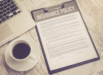 Paper that reads insurance policy on a desk next to a cup of coffee and a laptop